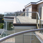 curved glass balcony with silver handrail